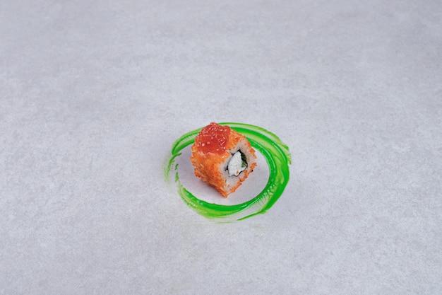 Rouleau de sushi de californie sur fond blanc avec anneau en plastique vert.