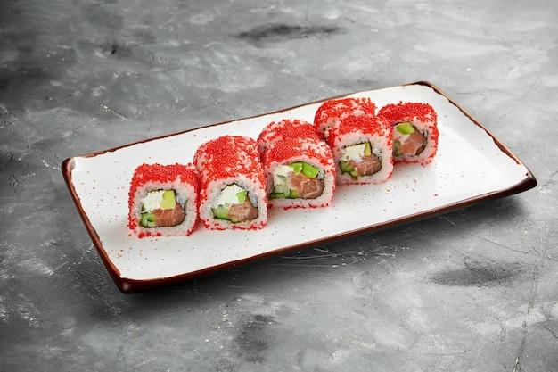 Rouleau de sushi californien classique au caviar tobiko avec saumon, concombre et fromage à la crème sur une plaque blanche sur une table grise. gros plan, mise au point sélective