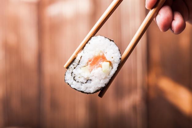 Rouleau de sushi close up entre paire de baguettes