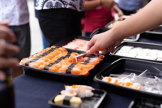 Rouleau de sushi de cueillette à la main de l'étal de nourriture au marché de rue d'événement