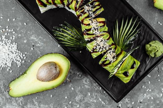 Rouleau de sushi dragon vert à l'anguille, à l'avocat, au concombre et au gingembre, accompagné de crevettes tempura frites