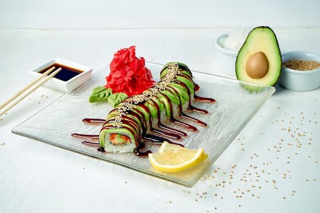 Rouleau de sushi dragon vert avec avocat et saumon, sauce unagi sur une plaque blanche