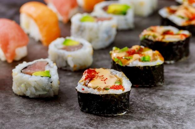 Rouleau de sushi avec du poisson cru sur fond gris. nourriture japonaise. fermer.