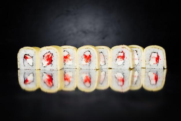 Rouleau de sushi fait de nori, riz mariné, philadelphie, fromage, massa caviar, crevettes