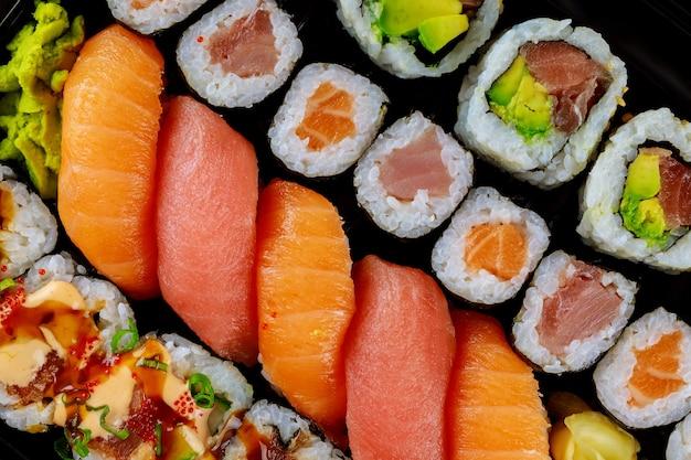 Rouleau de sushi frais colorés sur un plateau noir. nourriture japonaise. vue de dessus.