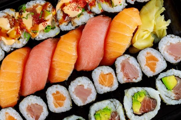 Rouleau de sushi frais sain serti de gingembre se bouchent. nourriture japonaise. vue de dessus.