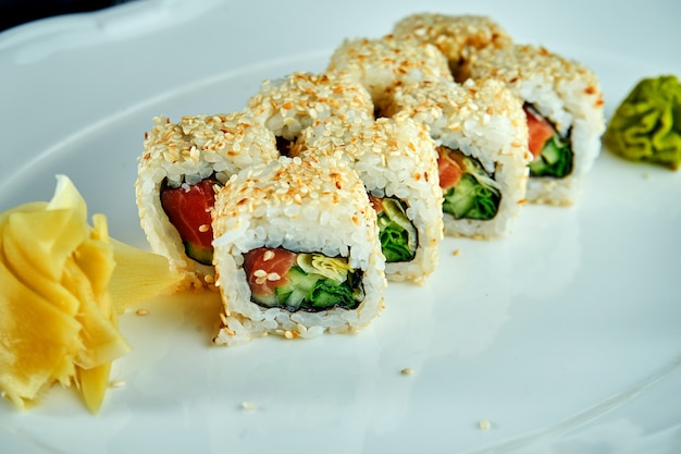 Rouleau de sushi futomak japonais appétissant au saumon, concombre dans une assiette blanche sur une surface en bois noir avec du gingembre et du wasabi. cuisine japonaise. rouleau de futomak
