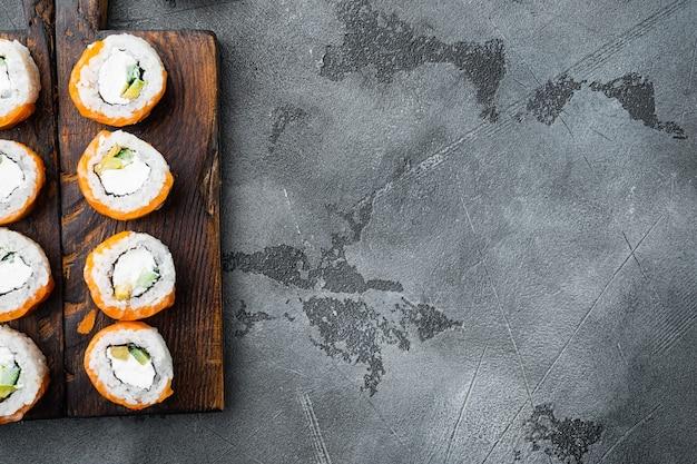 Rouleau de sushi geisha avec saumon brûlé au feu, bar, crevettes, avocat, sur pierre grise