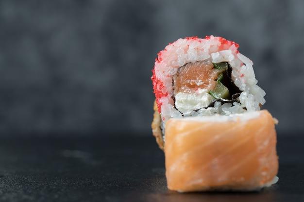 Rouleau de sushi avec des ingrédients mélangés isolé sur tableau noir.