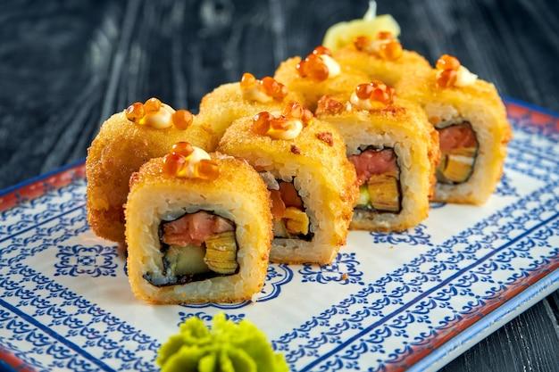 Rouleau de sushi japonais appétissant en tempura avec saumon, avocat et caviar dans une assiette bleue sur une surface en bois noire. cuisine japonaise