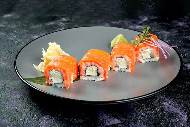 Rouleau de sushi japonais au saumon et fromage à la crème. roll philadelphia dans une plaque grise sur une surface noire