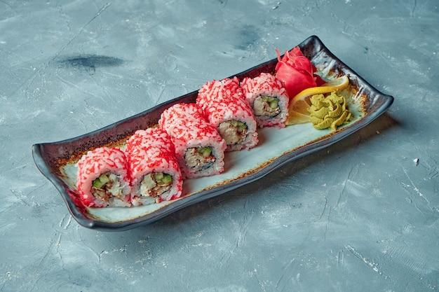 Rouleau de sushi japonais philadelphia avec fromage à la crème, anguille et caviar tobiko dans une assiette blanche sur une surface grise