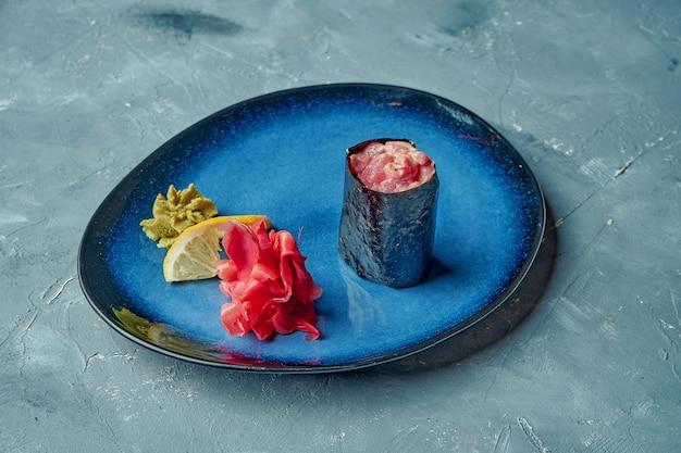 Rouleau de sushi japonais avec sauce épicée et thon dans une assiette bleue sur une surface grise. gunkan