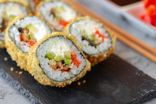 Rouleau de sushi japonais tempura servi sur plaque de pierre noire
