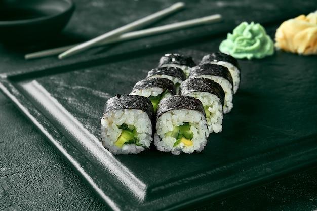 Rouleau de sushi maki au concombre. cuisine japonaise classique. livraison de nourriture. fond noir