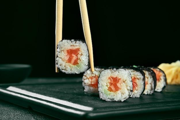 Rouleau de sushi maki au saumon. cuisine japonaise classique. livraison de nourriture. fond noir. les bâtons tiennent les sushis