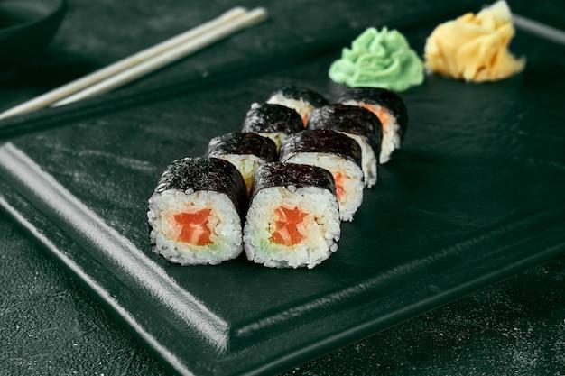 Rouleau de sushi maki au saumon. cuisine japonaise classique. livraison de nourriture. fond noir