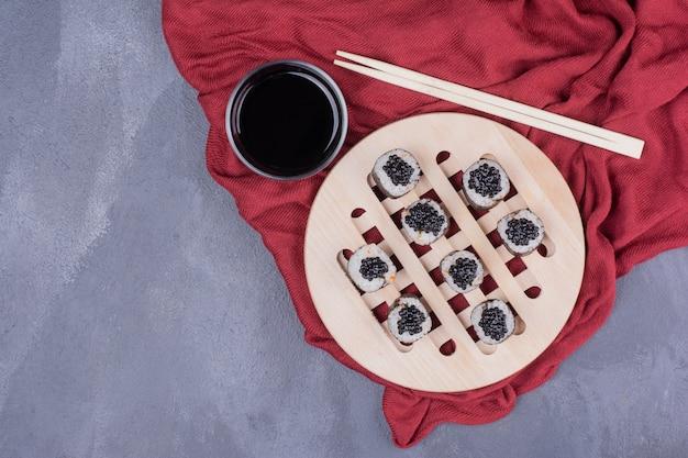 Rouleau de sushi maki traditionnel avec des baguettes et de la sauce soja sur une nappe rouge.