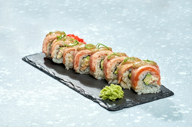 Rouleau de sushi de philadelphie avec saumon fumé, avocat, fromage à la crème et sauce sucrée sur une plaque noire sur fond clair