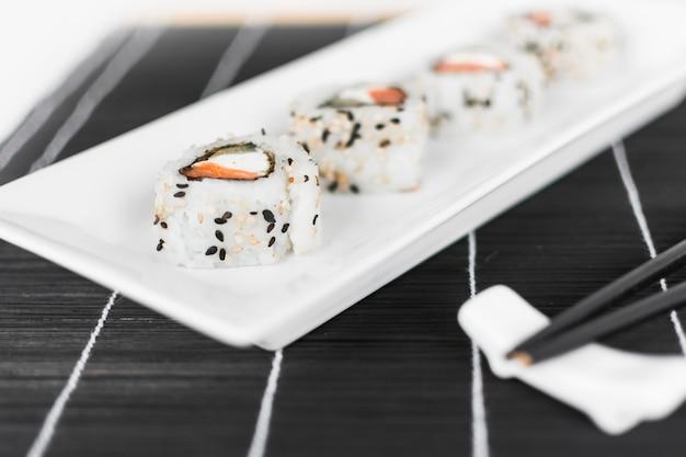 Rouleau de sushi sur un plateau blanc avec des baguettes