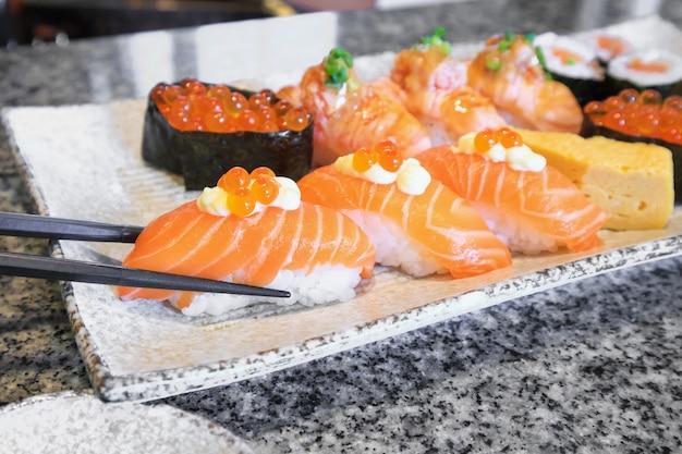 Rouleau de sushi sashimi saumon sertie de baguettes sur la plaque de la cuisine japonaise