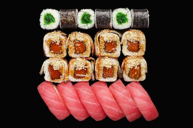 Rouleau de sushi avec saumon, anguille, mayonnaise japonaise, sauce unagi, graines de sésame, chuka, riz, nigiri au thon
