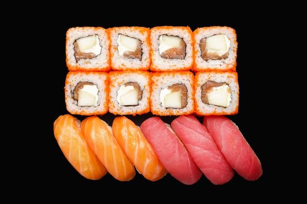 Rouleau de sushi avec saumon, fromage philadelphia, caviar masago, pomme. nigiri saumon, thon nigiri