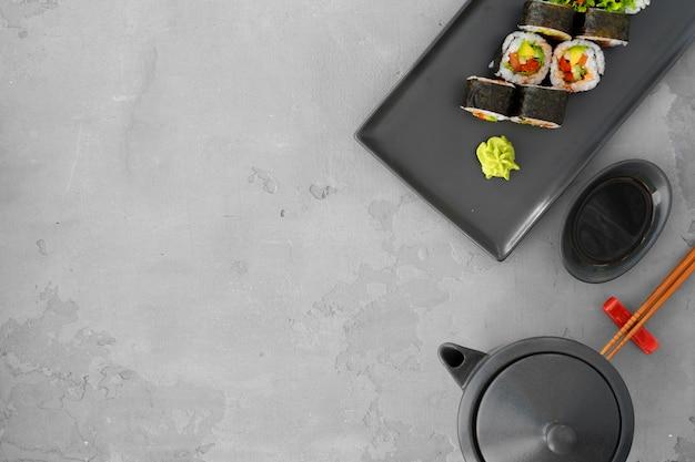 Rouleau de sushi végétarien avec des légumes sur la vue de dessus gris