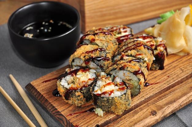 Rouleau de tempura au saumon sur une planche de bois