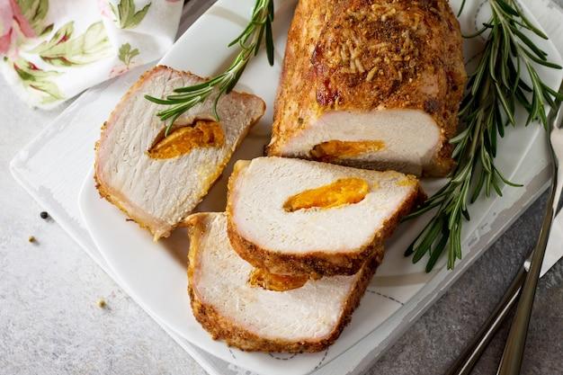 Rouleau de viande avec farce aux abricots et épices sur fond de pierre claire ou d'ardoise