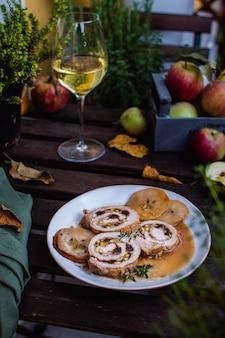 Rouleau de viande rempli de pistaches et de pruneaux, verre de vin blanc sur une table en bois rustique