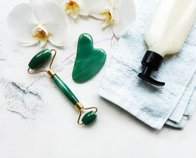 Rouleau de visage en jade pour la thérapie de massage du visage de beauté. mise à plat sur une table en marbre wtite