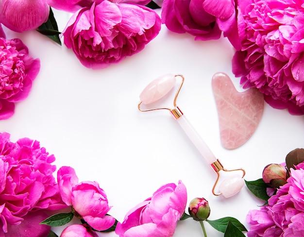 Rouleau de visage en jade pour la thérapie de massage du visage de beauté et les pivoines roses.