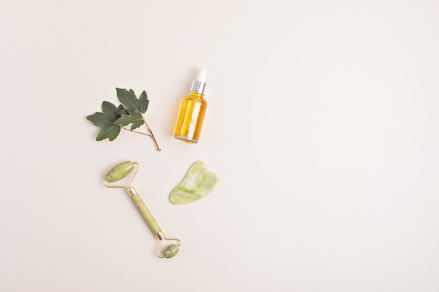 Rouleau de visage en jade vert, pierre de gua sha, huile essentielle. concept de soins naturels de la peau. vue de dessus, mise à plat