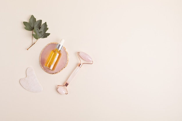 Rouleau de visage en quartz rose, pierre de gua sha, huile essentielle. concept de soins naturels de la peau. vue de dessus, mise à plat