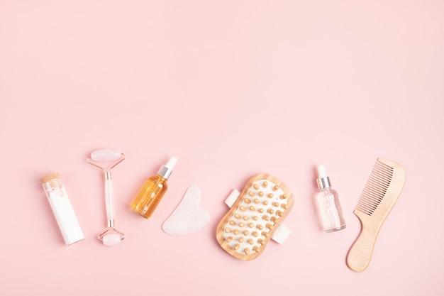 Rouleau de visage en quartz rose, pierre de gua sha, huile essentielle, masseur. concept de soins de la peau réutilisables naturels. vue de dessus, mise à plat