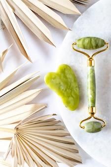 Rouleau de visage vert et masseur gua sha fabriqués à partir de pierre naturelle de néphrite de jade sur fond de marbre