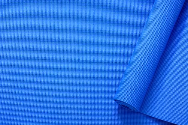Rouleau de vue de dessus du fond de texture de tapis de yoga de couleur bleue, sport et concept d'exercice