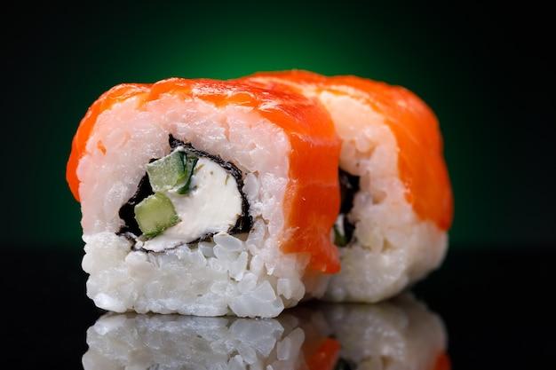 Rouleaux au poisson rouge et concombre sur fond noir