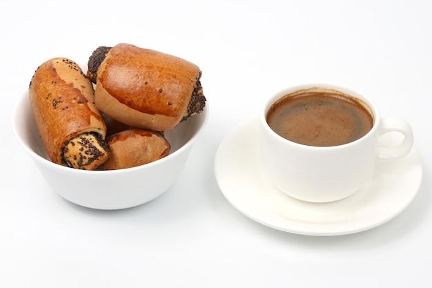 Rouleaux aux graines de pavot et blanc tasse de café noir. desserts