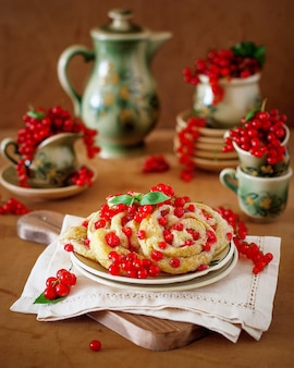 Rouleaux de biscuits au fromage cottage aux groseilles rouges sur une plaque en céramique avec service à café ou à thé en céramique vintage, heure du thé, petit-déjeuner, bonbons d'été