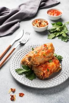 Rouleaux de chou avec du boeuf, du riz et des légumes dans l'assiette. feuilles de chou farcies à la viande. table en béton gris