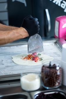 Rouleaux de crème glacée sautés dans un moule à congélation. glace roulée, dessert à la crème glacée fait à la main. machine à crème glacée frite avec poêle réfrigérée en acier.