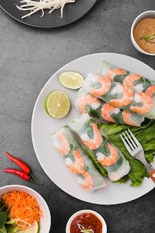 Rouleaux de crevettes sur une assiette avec citron vert et sauce