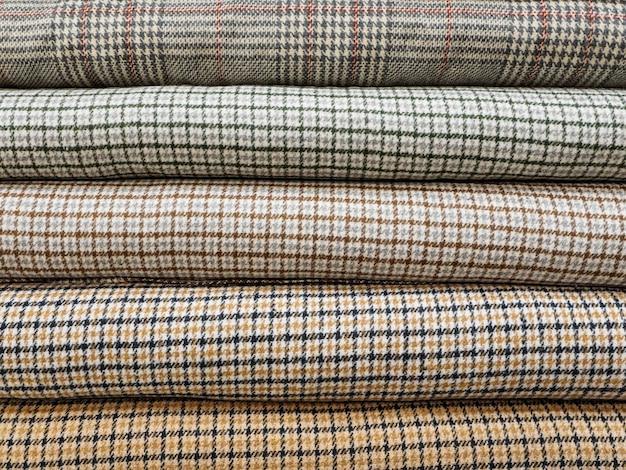 Rouleaux de différents tissus à carreaux pour coudre des manteaux en gros plan.