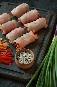 Rouleaux faits maison avec poitrine de poulet fraîche aux herbes, tranches de carottes, poivrons sur une planche à découper sombre. l'équilibre d'une alimentation saine. cuisine. fond en bois foncé.