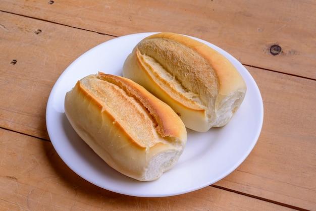 Rouleaux français. pains brésiliens sur une plaque blanche sur une table en bois.