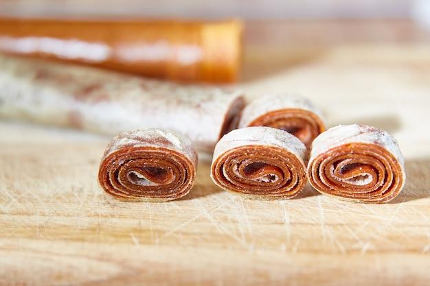 Rouleaux de fruits faits maison sur une planche de bois, pastilles de bonbons pour un concept de petit-déjeuner sain, espace copie
