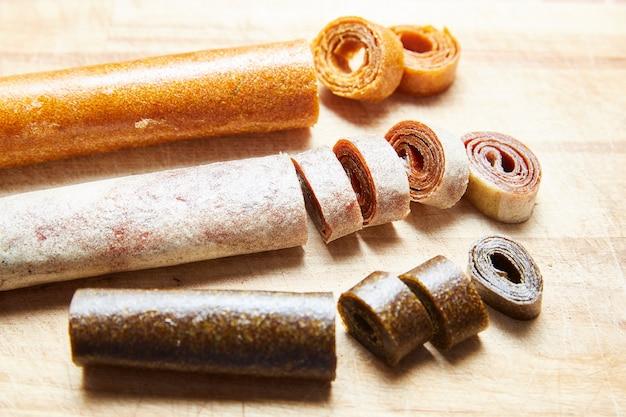 Rouleaux de fruits faits maison sur une planche de bois, pastilles de bonbons pour un concept de petit-déjeuner sain.