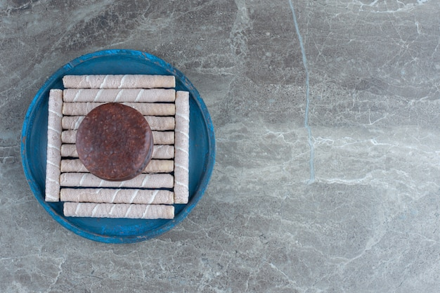 Rouleaux de gaufres fraîches avec biscuit au chocolat sur une plaque en bois bleue.